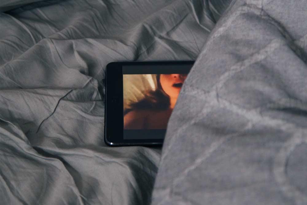 film porno su tablet sul letto