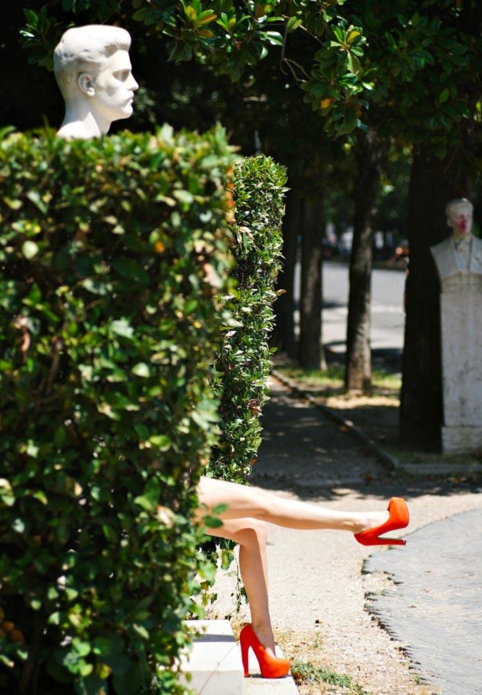 piedi con scarpe rosse con tacco che spuntano da una siepe