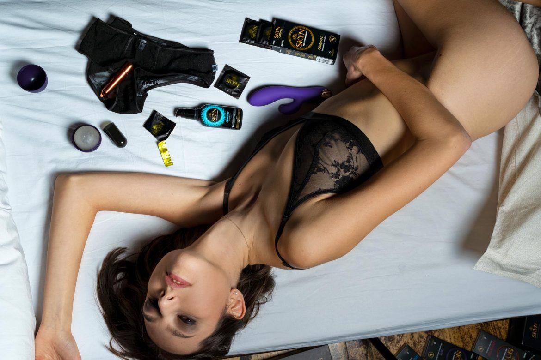 Preservativi lubrificante e sex toy Skyn sparsi sul letto